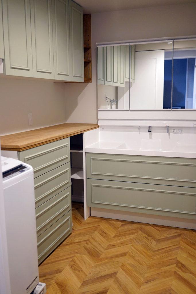 ヘリンボーンの床材を敷いたパウダールーム。リクシルの洗面台エルシィの扉を特注品に変更しています。