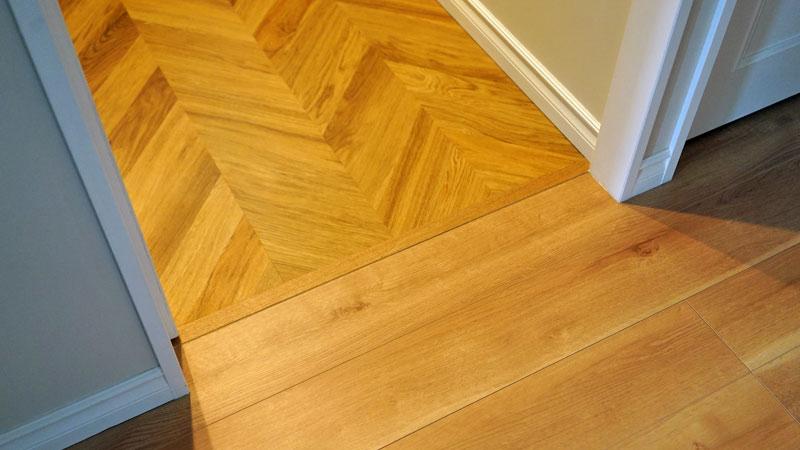 ユーティリティルーム(洗面所)のヘリンボーン柄の床材との境にも敷居があります。