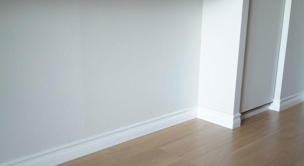 純白のモールディングの巾木が際立つ、薄いグレーの壁紙